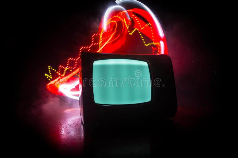 Old vintage red TV with white noise on dark toned foggy background. Retro old Television reciever no signal. Selective focus stock photos