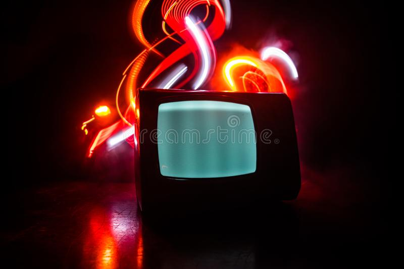 Old vintage red TV with white noise on dark toned foggy background. Retro old Television reciever no signal stock photography