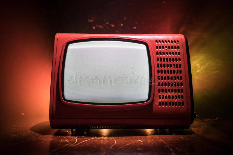 Old vintage red TV with white noise on dark toned foggy background. Retro old Television reciever no signal stock image