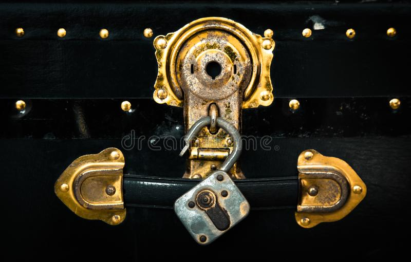 Old vintage retro box and padlock from treasure vault pirate´s chest in gold color with rusty metal details.  stock images