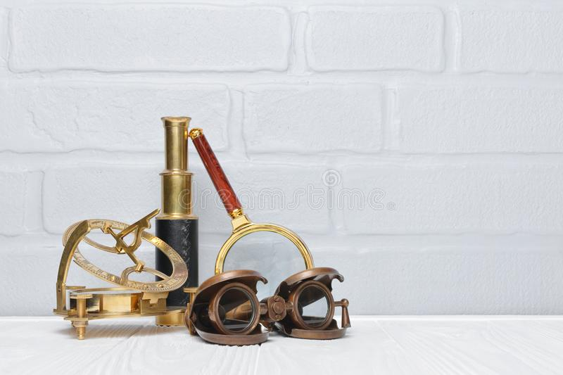 Old vintage retro compass, binoculars and spyglass as accessories for styled journey with copy space. On gray brick wall background royalty free stock photos