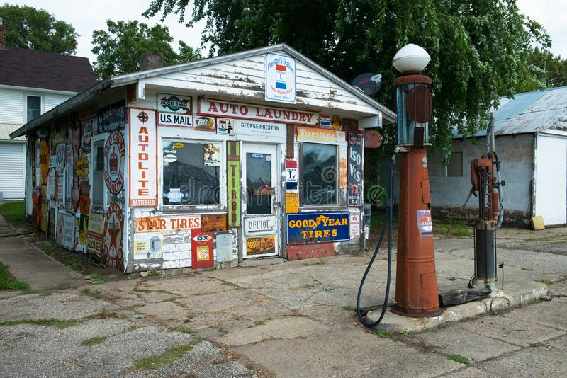 Old Vintage Retro Gas Station. Old vintage retro gas or filling station. The building is covered with street and road signs from another era. In front is an