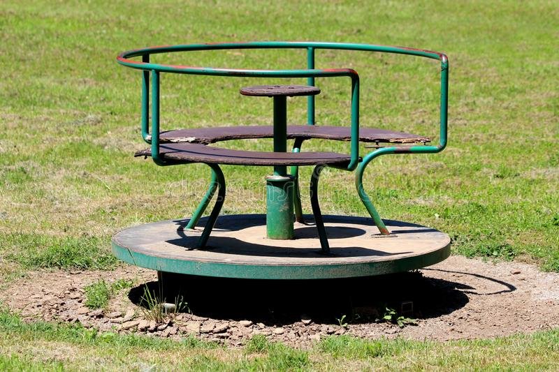 Old vintage retro partially rusted outdoor public playground equipment made of metal and cracked wood in shape of roundabout royalty free stock photography