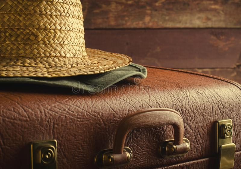 Old vintage, retro suitcase and straw hat on dark background. Travel concept, Toned royalty free stock photos