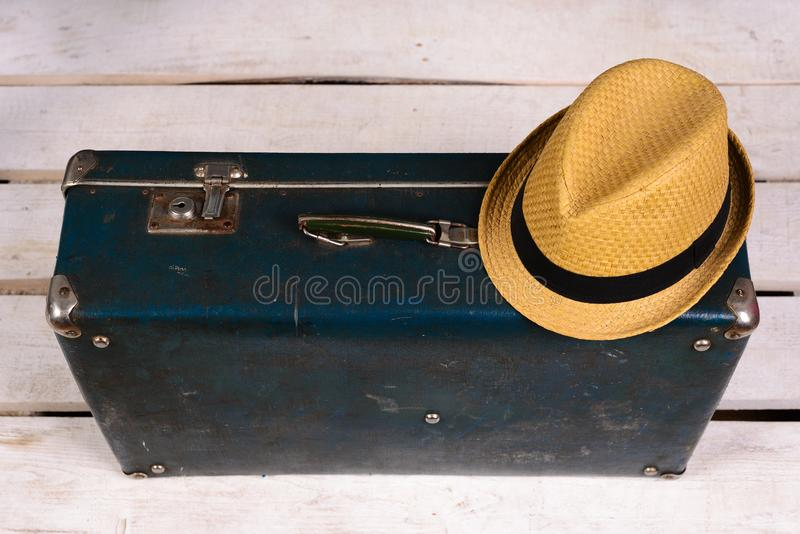 Old vintage, retro suitcase and a straw hat on a white wooden floor. stock photography
