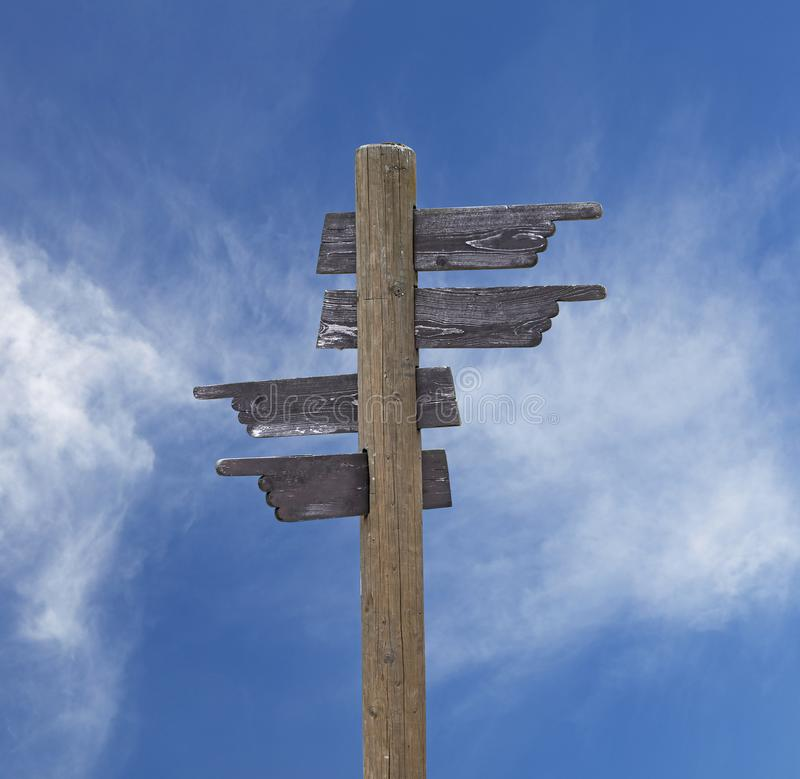 Old wooden road sign with four arrows over sky royalty free stock photo