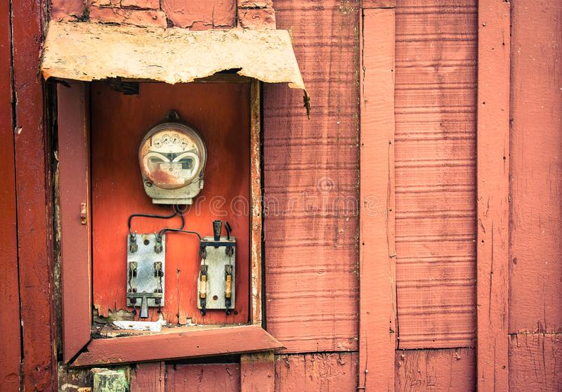 Old vintage and rusted analog electricity meter counter. Used for measurements in kWh of electricity usage with two switches on a red cracked and peeling wooden royalty free stock photos