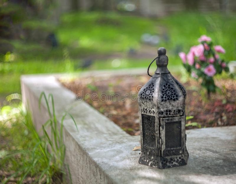 Old vintage rusted lantern standing on a gravestone with a blurred background stock photography