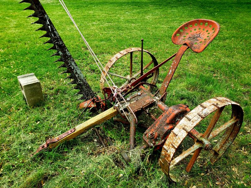 Old vintage rusty  farming machine on grass royalty free stock photography