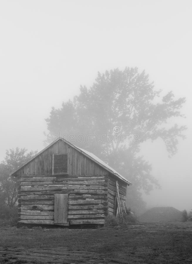 Old vintage sawn log cabin in the fog bw royalty free stock photography