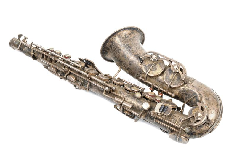 Old vintage saxophone. Old rusty meta brokenl vintage saxophone on a withe background stock photography