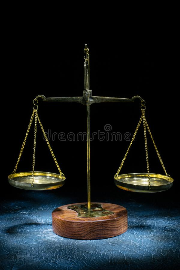 Old vintage scales of justice stand on a stone background. Picture taken with a light brush stock photos