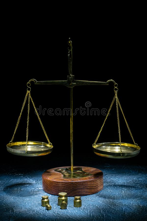 Old vintage scales of justice with weights stand on a stone background. Picture taken with a light brush royalty free stock image