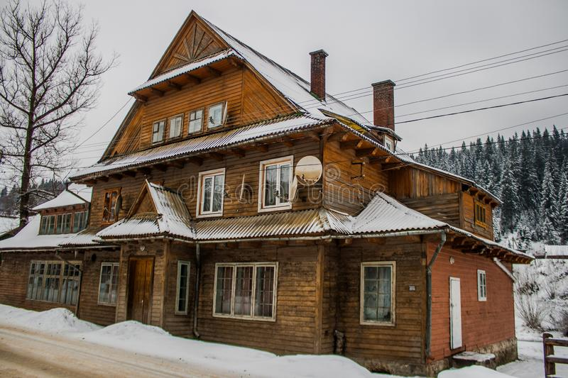 Old vintage snowy wooden house. Winter. Mountains and forest. S. Village home stock image