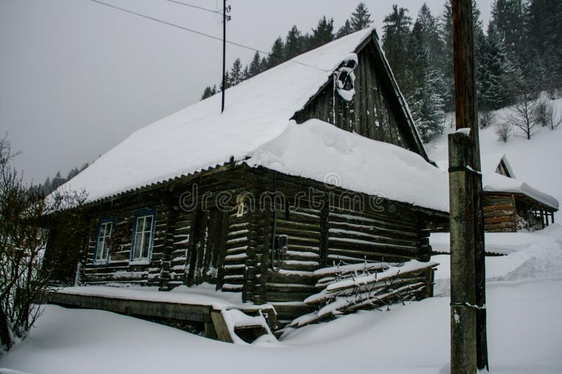 Old vintage snowy wooden house. Winter. Mountains and forest. S. Village home stock photography