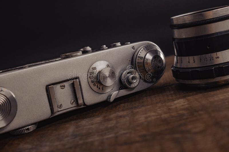 Old vintage soviet camera with lens on wooden background. Voronezh Russia 02.02.2019 old vintage soviet camera with lens on wooden background film antique retro stock photos