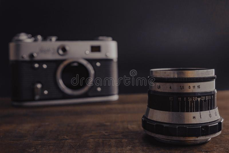 Old vintage soviet camera with lens on wooden background. Voronezh Russia 02.02.2019 old vintage soviet camera with lens on wooden background film antique retro stock images