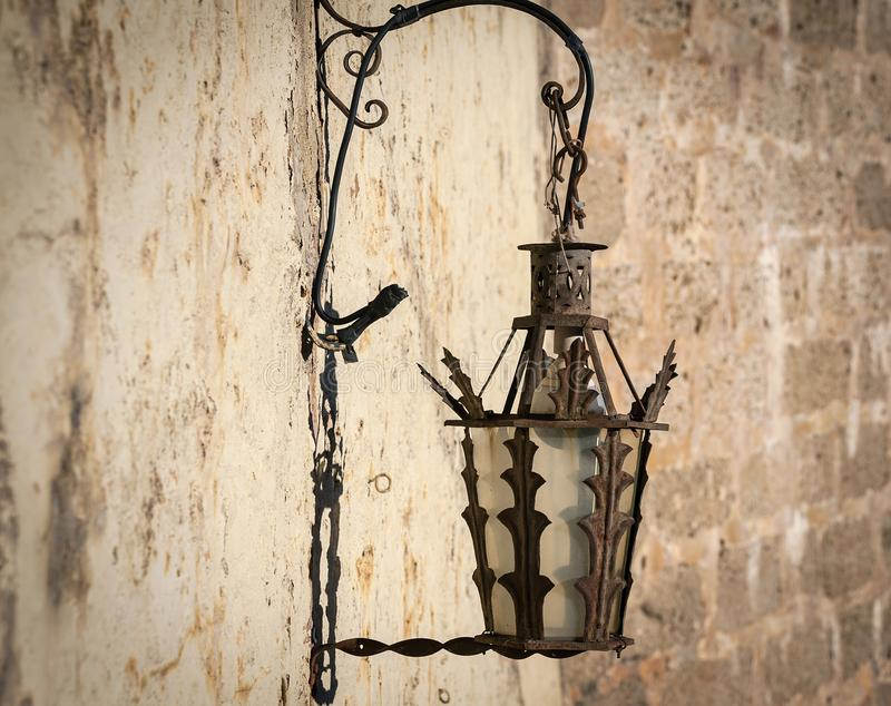 Old vintage street lamp mounted on wall at street of Ronda town, Spain.  royalty free stock photography
