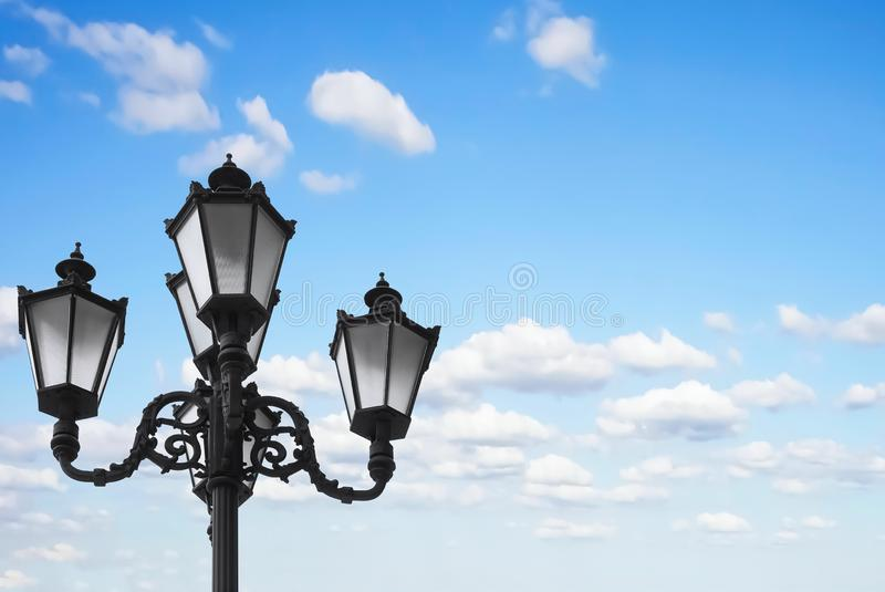 Old vintage street lamp post or lantern with light bulbs against a beautiful blue sky with white clouds background royalty free stock photos