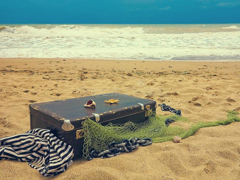 Old vintage suitcase for travel and family vacations lies on the beach. Sea shore ocean. Photo in a trendy retro style.  stock photos