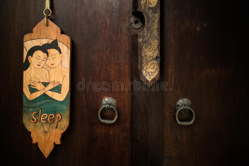 Old vintage Thai style of do not disturb sign hanging in a hotel. For private relax and sleep royalty free stock images