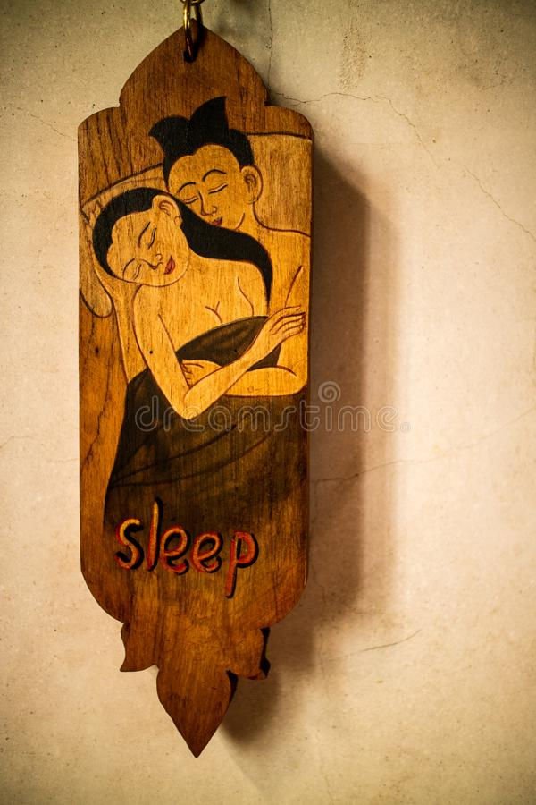 Old vintage Thai style of do not disturb sign hanging in a hotel. For private relax and sleep royalty free stock photo