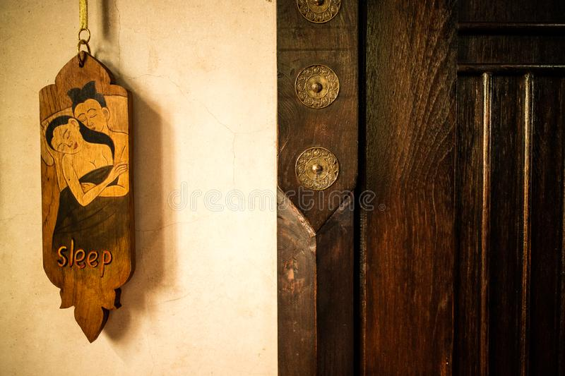 Old vintage Thai style of do not disturb sign hanging in a hotel. For private relax and sleep stock photo