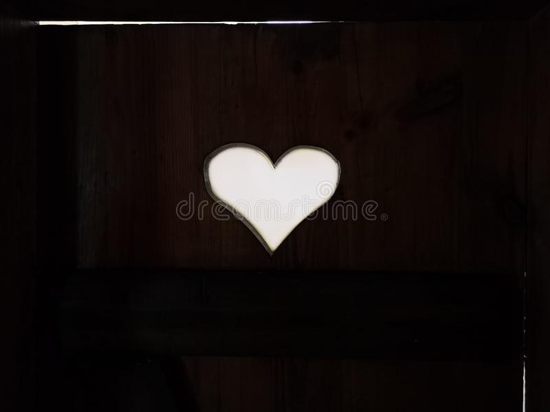 Old vintage toilet door with a heart shaped hole, filters applied stock photo