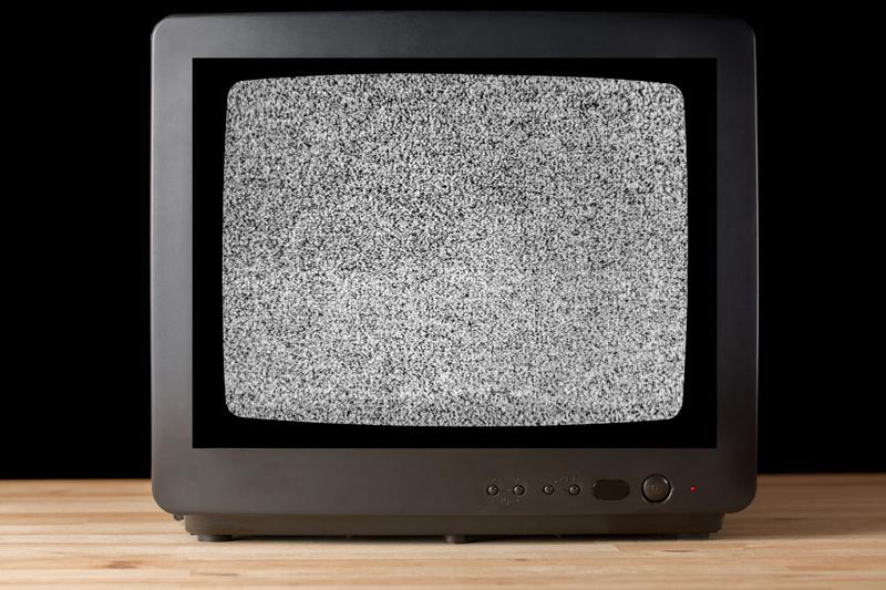 Old vintage TV set televisor on wooden table againt black background with no signal television grainy noise effect on the screen. No signal retro vintage stock image