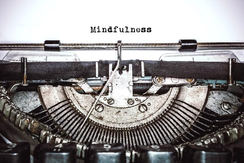 Old vintage typewriter, retro machine with white sheet of paper and typed text. `mindfulness`, copy space, close up stock photos