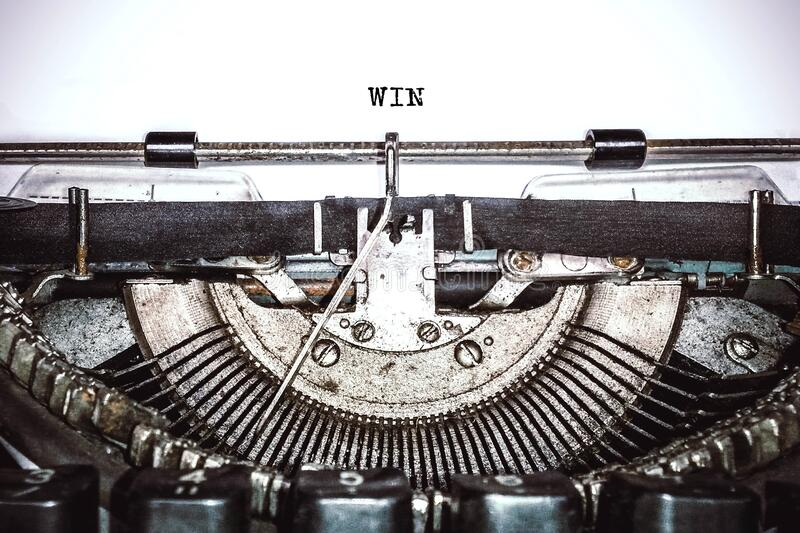 Old vintage typewriter, retro machine with white sheet of paper and typed text. `win`, copy space, close up royalty free stock image
