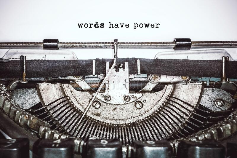 Old vintage typewriter, retro machine with white sheet of paper and typed text. `words have power`, copy space, close up royalty free stock photo