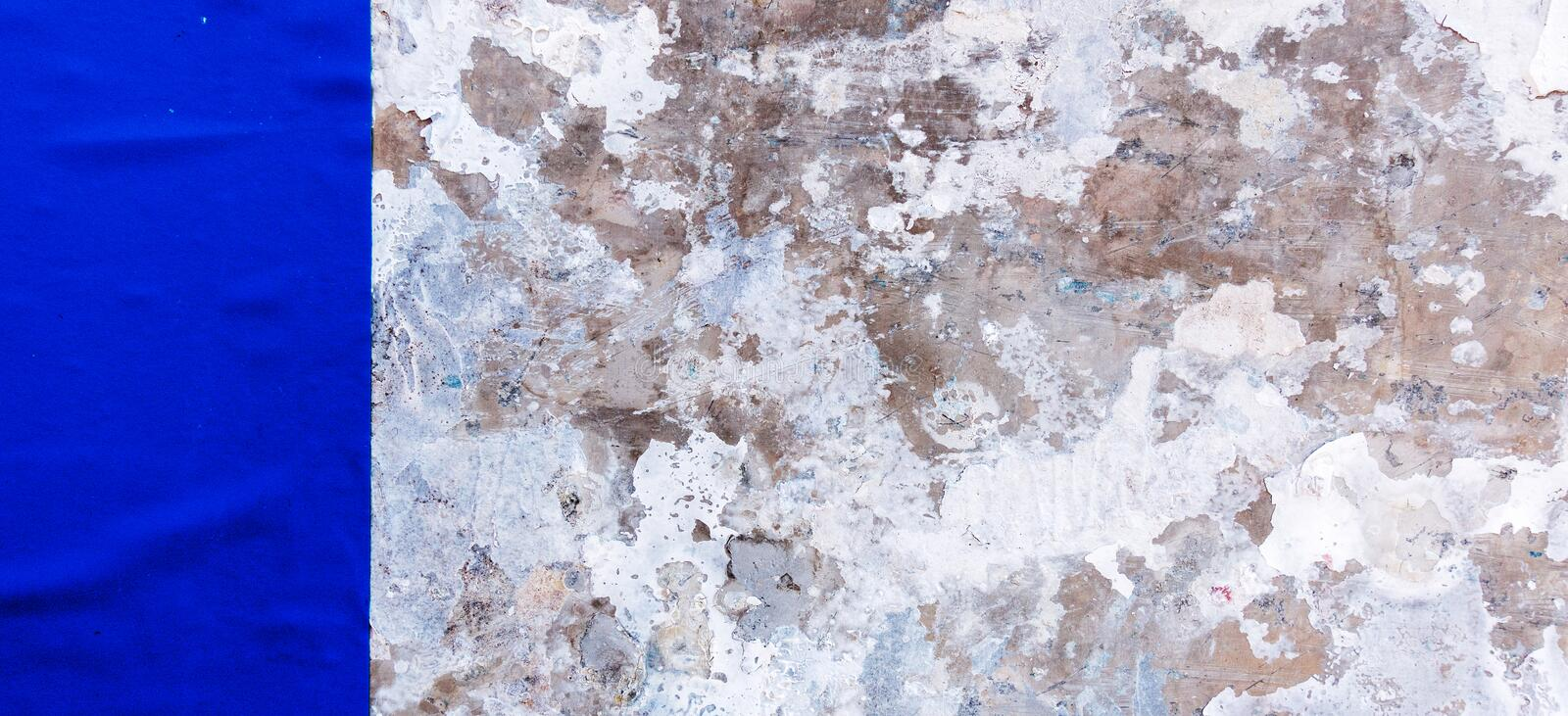 Old vintage weathered dirty grungy plaster painted wall with blue old poster background.  royalty free stock images
