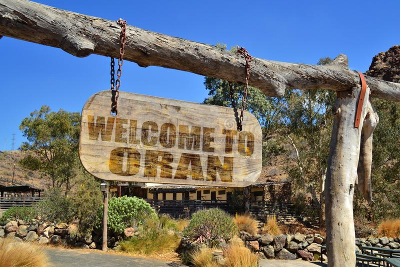 Old vintage wood signboard with text welcome to Oran. Hanging on a branch royalty free stock photo
