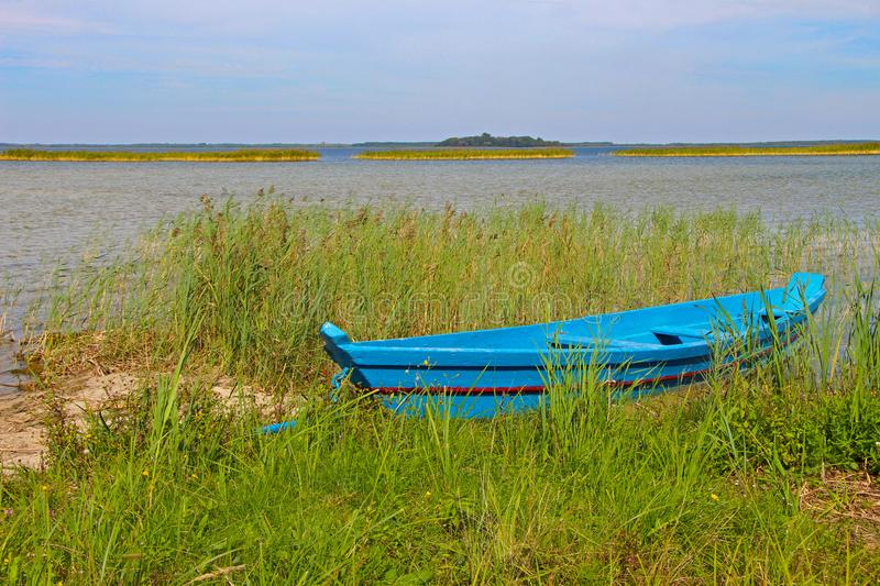 Old vintage wooden blue fishing boat on the green grass with horizon royalty free stock image