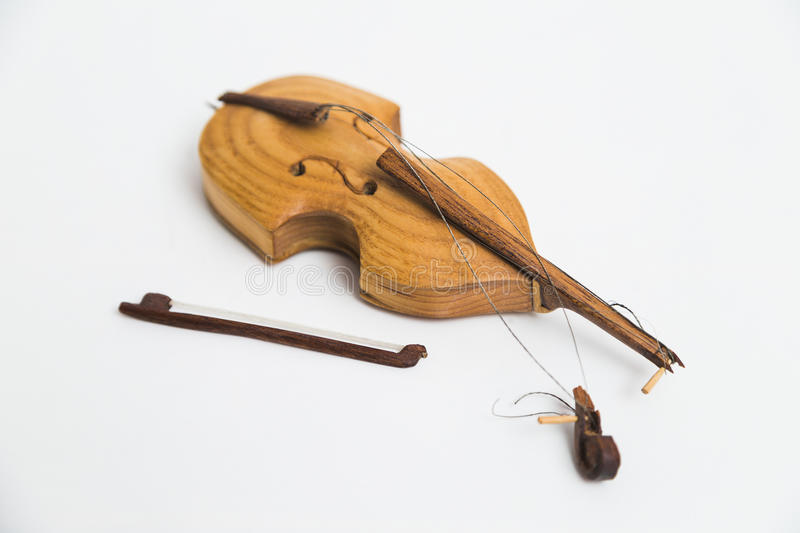Old vintage wooden broken violin with bows on white background. stock image