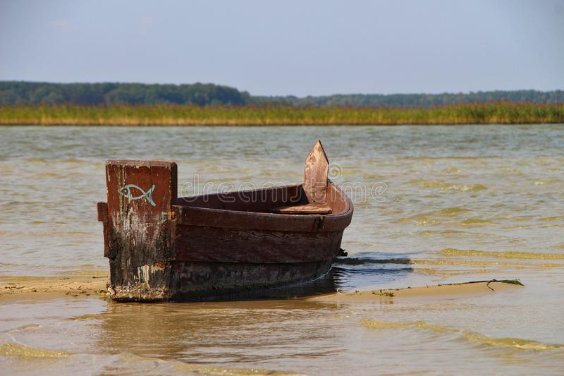 Old vintage wooden brown fishing boat on the clear water with horizon stock photos