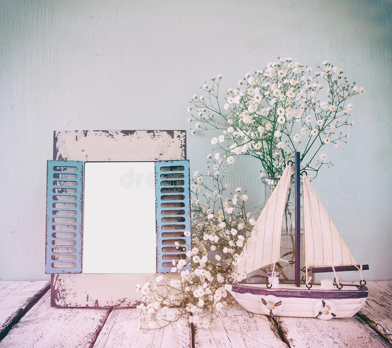 Old vintage wooden frame, white flowers and sailing boat on wooden table. vintage filtered image. nautical lifestyle concept stock photo