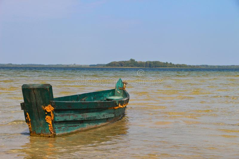 Old vintage wooden green fishing boat on the clear water with horizon royalty free stock photos