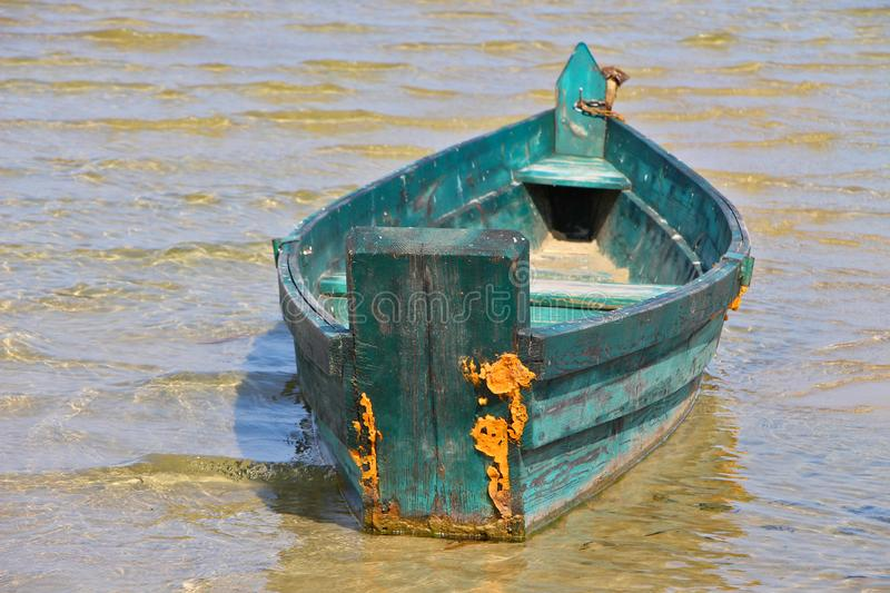 Old vintage wooden green fishing boat on the clear water royalty free stock photos