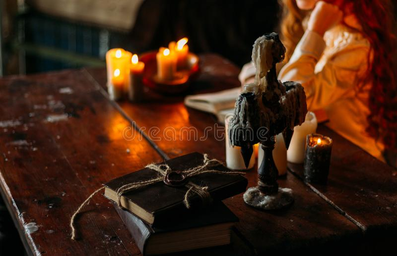 On the old vintage wooden table is a candlestick with candles. A red-haired girl in vintage clothes is sitting at the table, readi royalty free stock image
