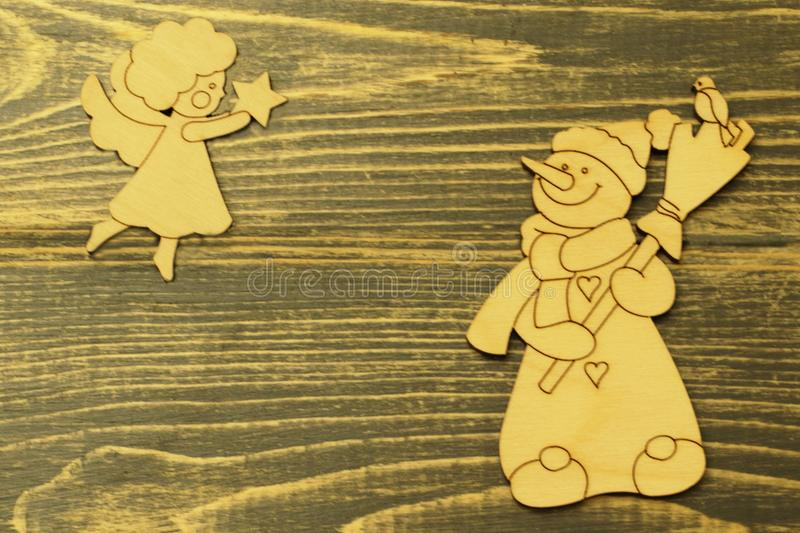 Old vintage wooden toys. Cheerful snowman with broom and figure of angel soaring in height with Christmas star on old dark natural royalty free stock photo