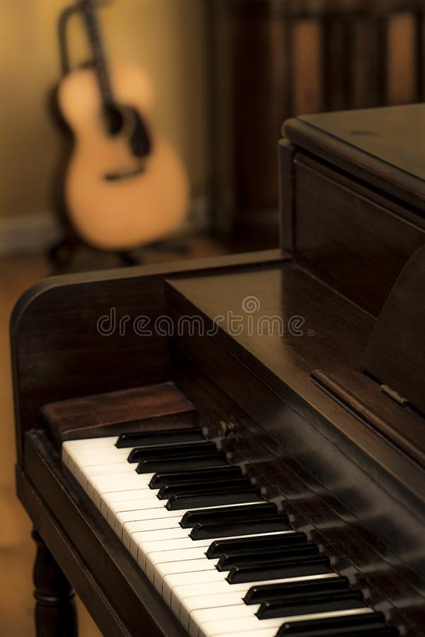 Old vintage wooden upright piano with keys and acoustic guitar a royalty free stock image