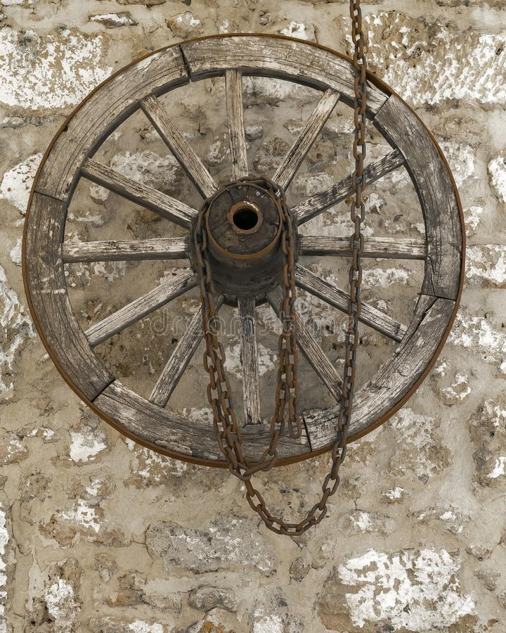 Old vintage wooden wheel with rusty metal chain hanging on a stone house wall.  stock photography