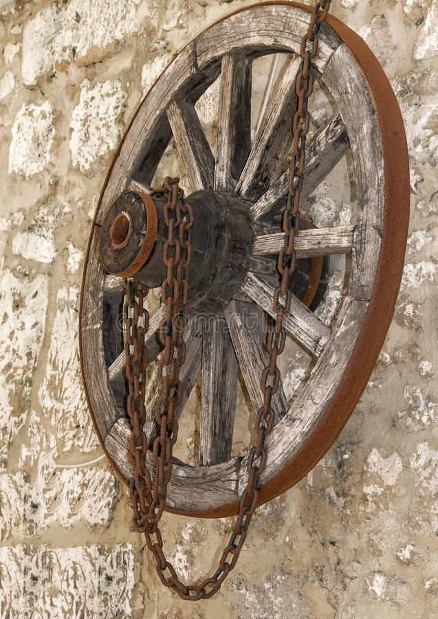 Old vintage wooden wheel with rusty metal chain hanging on a stone house wall. Side view. Old vintage wooden wheel with rusty metal chain hanging on a stone stock photography