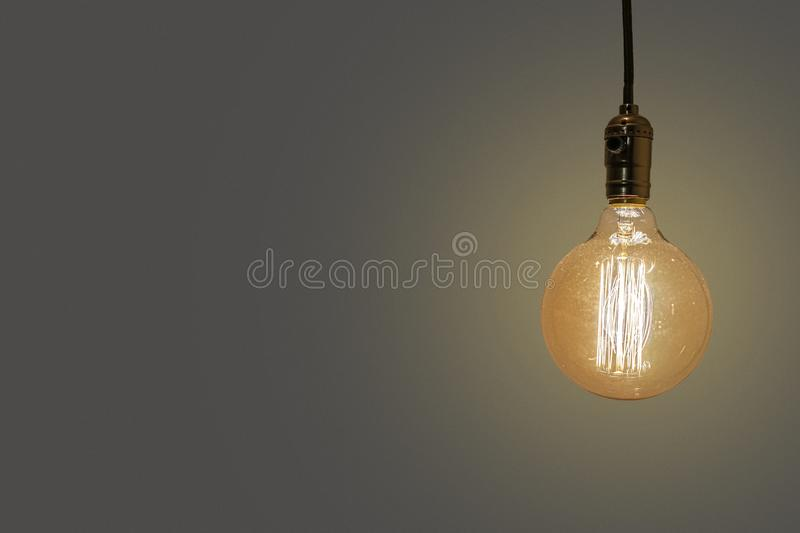 Old vintage yellow  electric lightbulb on beige background royalty free stock photo