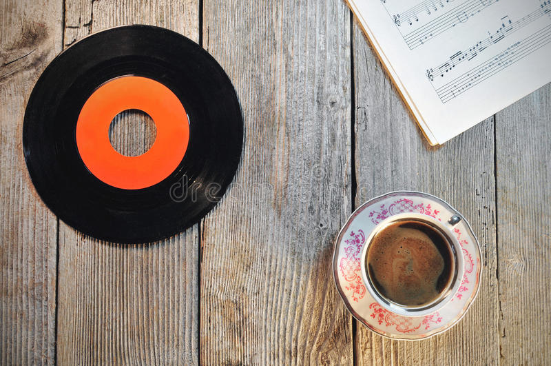 Old vinyl record, cup of coffee and music notes. On a wooden table stock photos