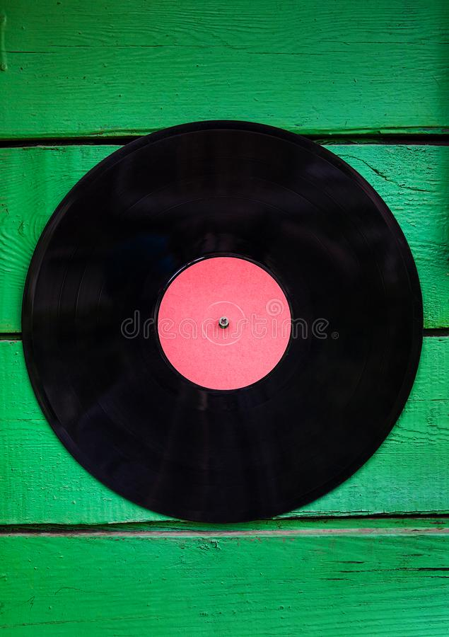 Old Vinyl Record. On the Green Planks Background stock photography