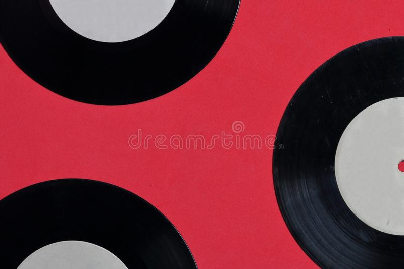 Old vinyl records. Worn and dirty. They lie on the surface of coral color royalty free stock image
