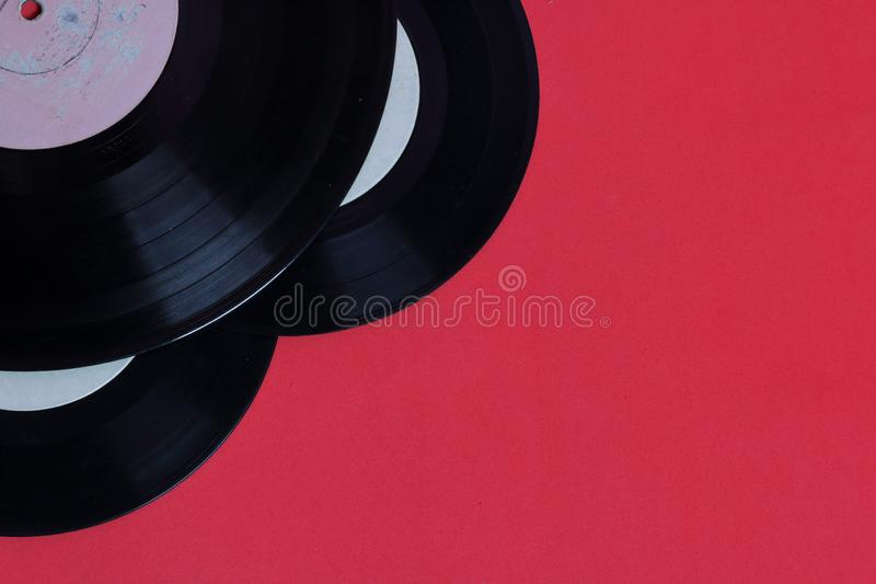 Old vinyl records. Worn and dirty. They lie on the surface of coral color royalty free stock images